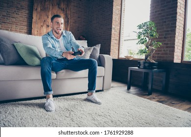 Photo of domestic handsome guy relaxing stay home quarantine time playing video games playstation football final match sit cozy sofa modern interior living room indoors