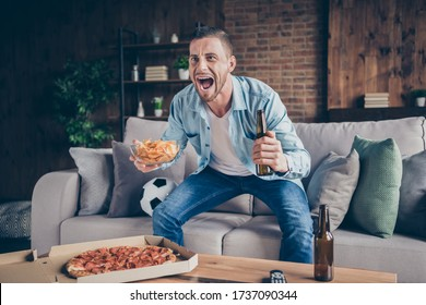 Photo of domestic handsome guy stay home quarantine time watch television eat pizza drink beer sit cozy sofa football season opening support favorite team modern interior living room indoors