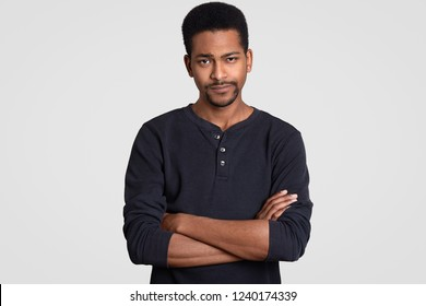 Photo of doubtful serious dark skinned man keeps hands crossed, hears some information, dressed in casual clothes, models against white background. Displeased Afro American guy with folded arms