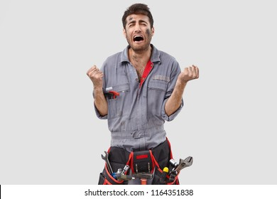 Photo of downcast stressed engineer clenches fists desperately, being despondent by bad work conditions, feels tired of constant hard labour, dressed in casual clothes, poses against white background
