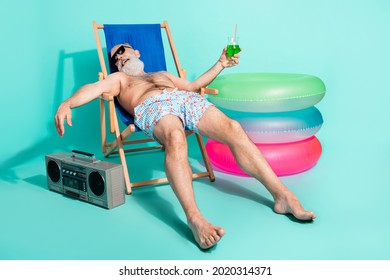 Photo of drunk funny pensioner shirtless lying beach chair drinking alcohol listening boom box isolated teal color background