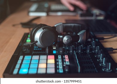 Photo of earphones on controller or DJ instruments for creative music. Objects lying on wooden table in black modern and sound studio with style interior