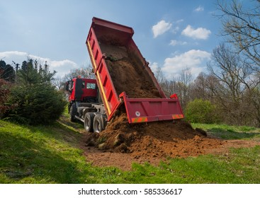 Photo of earthworks with red truck dumping and tipping raw earth soil. Tip truck preparing ground for new housing estate with green grass, trees and blue sky. Land management, urban growth, regulation