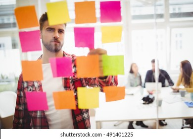 Photo editor looking at multi colored sticky notes on glass in meeting room at creative office