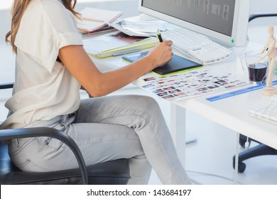 Photo editor pointing using graphics tablet in her office