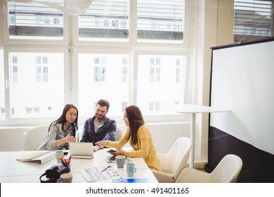 Photo editors using laptop in meeting room at office