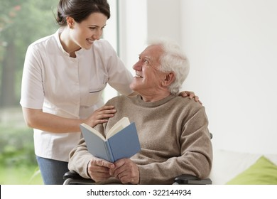 Photo of elderly man reading book and his private nurse