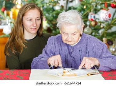 Photo of elderly woman having breakfast with her caregiver