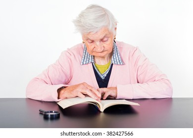 Photo of elderly woman reading a book
