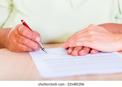 Photo of an elderly woman sign the testament