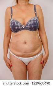 Photo of an elderly woman in underwear on a white isolated background. Hands down along the body. concept for medicine and cosmetology. front view.