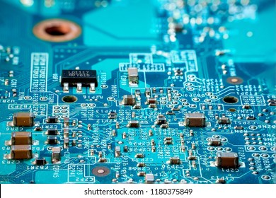 Photo of  electric component in electronic device, contain small resistor, small capacitor, microchip and capacitor on blue printed circuit board