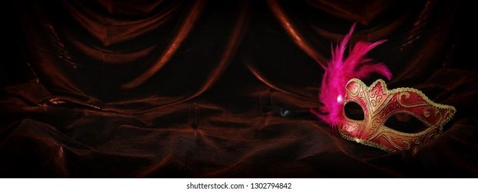 Photo of elegant and delicate gold, red venetian mask over dark velvet and silk background