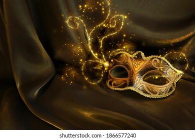 Photo of elegant and delicate gold Venetian mask over dark silk background