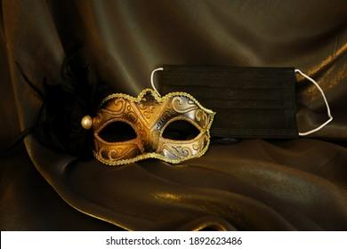 Photo of elegant and delicate gold Venetian mask over black silk background. Coronavirus prevention concept