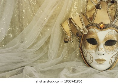 Photo of elegant and delicate Venetian mask over pastel blue and gold chiffon background