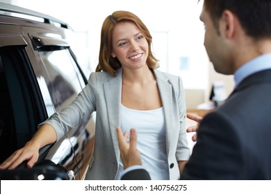 Photo of elegant woman speaking to consultant in automobile center