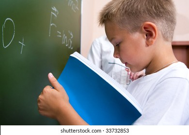 Photo of elementary student holding copybook and consulting his notes by the blackboard