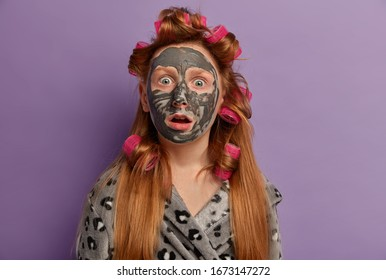 Photo of embarrassed ginger teenager gazes surprised at camera, opens mouth, expresses disbelif, wears nourishing mask on face, hair curlers, being very emotive, isolated on purple background