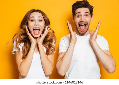 Photo of emotional couple man and woman in basic clothing screaming in surprise or delight and raising arms isolated over yellow background