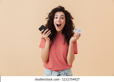Photo of emotional excited pretty young curly woman isolated over beige background using mobile phone holding credit card.