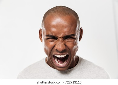 Photo of emotional screaming young african man standing isolated over white background. Looking camera.