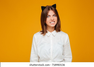 Photo of emotional young lady dressed in crazy cat halloween costume over yellow background.