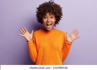 Photo of emotive happy lady shows palms, exclaims loudly with optimism, wears orange jumper, isolated over purple background, enjoys life, feels overjoyed. People, excitement and joy concept