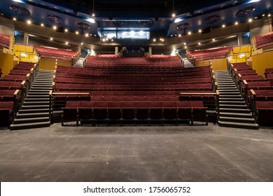 Photo of an empty cinema or theatre showing rows of red foldable seats in the empty building - Shutterstock ID 1756065752