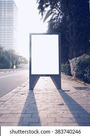 Photo empty lightbox on the bus stop. Vertical mockup, sunlight