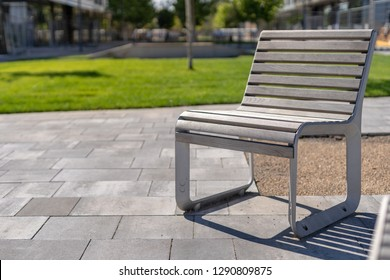 Photo of empty street or public park place with wooden chairs standing outdoor against blurred background