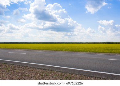 Photo of an empty summer road. On the road there are no cars, the weather is cloudy