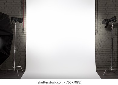 Photo of an empty white background in photographic studio with modern lighting equipment. Empty space for your text or objects