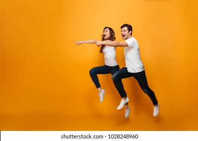 Photo of energetic beautiful couple posing together on camera while running or jumping and pointing fingers on copyspace along background
