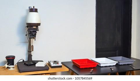 Photo enlarger and accessories in darkroom