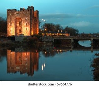 photo epic beautiful famous world eurepean breathtaking bunratty castle in west of ireland, county clare. irish castle and pub, durty nellies nelly's at night with water reflection.