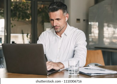 Photo of european businessman 30s wearing white shirt and wireless earphones sitting at table in office and working at laptop