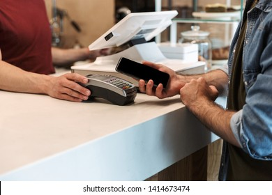 Photo of european man wearing denim shirt paying cellphone in cafe while waiter holding payment terminal