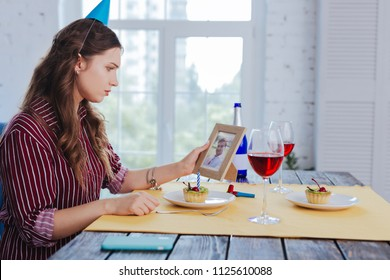 Photo of ex. Sad pessimistic woman feeling cheerless and lonely while looking at photo of her ex boyfriend