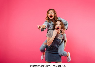 Photo of excited amazing two women friends have fun isolated over pink background. Looking camera pointing.