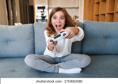 Photo of excited nice girl smiling and playing video game with joystick while sitting on couch at home