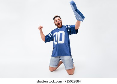 Photo of excited screaming man fan in blue t-shirt sitting isolated over white background. Looking aside wearing number one fan glove finger.