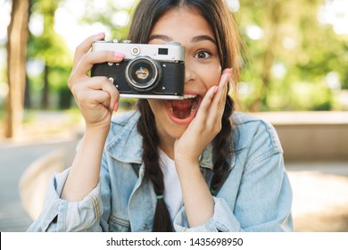 Photo of excited shocked optimistic happy cute young student girl wearing eyeglasses sitting on bench outdoors in nature park holding camera photographing.