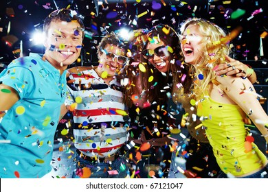 Photo of excited teenagers embracing at party under falling confetti