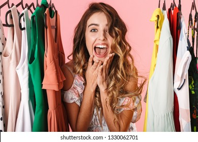Photo of excited woman in dress standing inside wardrobe rack full of clothes isolated over pink background
