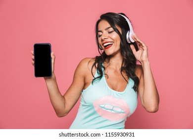 Photo of excited woman in swimwear isolated over pink wall background showing display of mobile phone listening music with headphones.