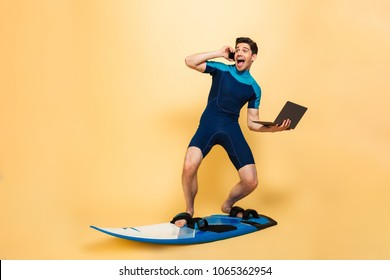 Photo of a excited young man dressed in swimsuit isolated over yellow background on surfing board talking by phone using laptop computer.