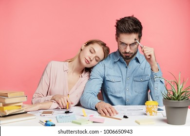 Photo of exhausted sleepy female tired after hard work on course or diploma paper, work with scientific literature. Focused brunet handsome man studies document, tries understand information