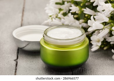 Photo of face cream over wooden table