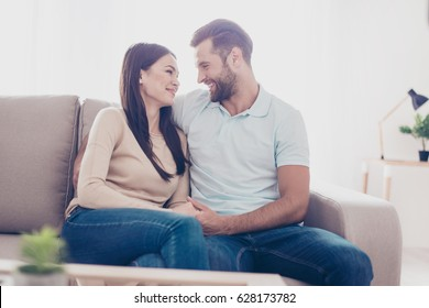 Photo of a family couple sitting on the sofa at home and spending their free time together